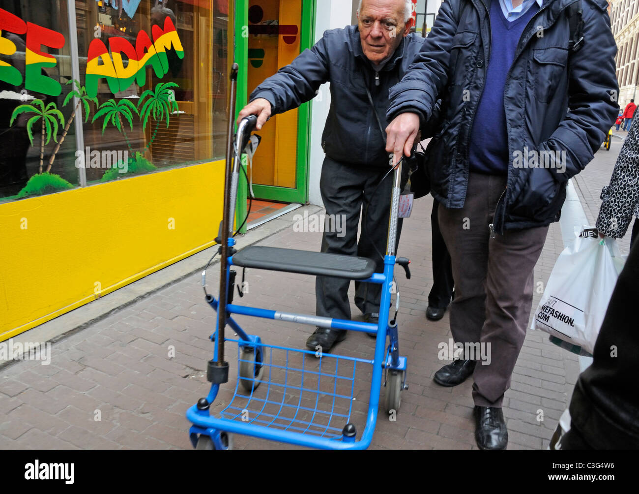 Amsterdam, Netherlands. Old man walking with help of wheeled walking ...