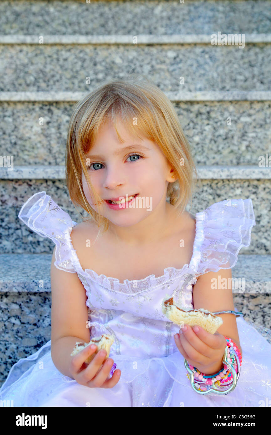 blond children girl eating chocolate sandwich princess dress on granite stairs Stock Photo