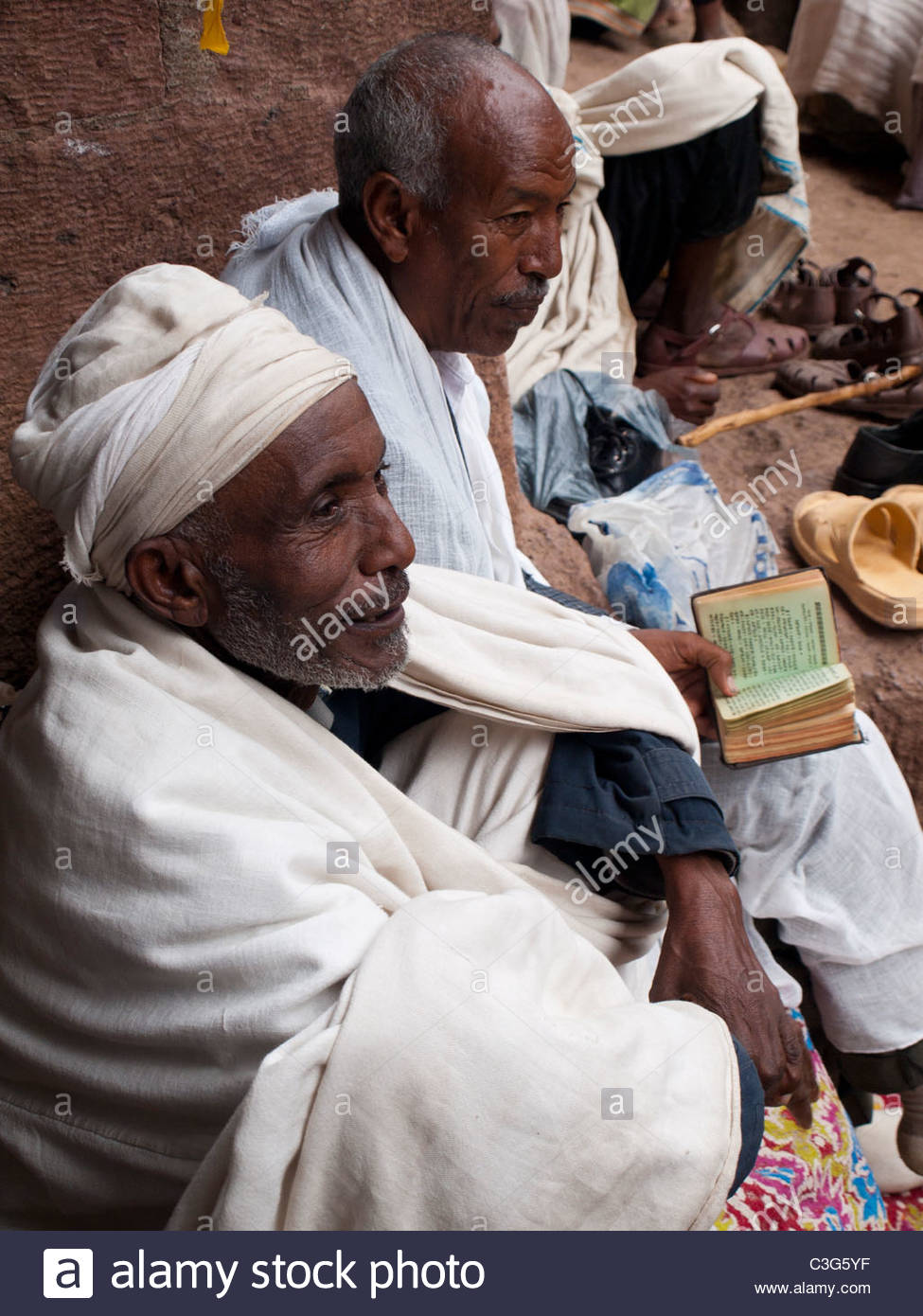 Two pilgrims read the Bible outside church in Lalibela - Stock Image