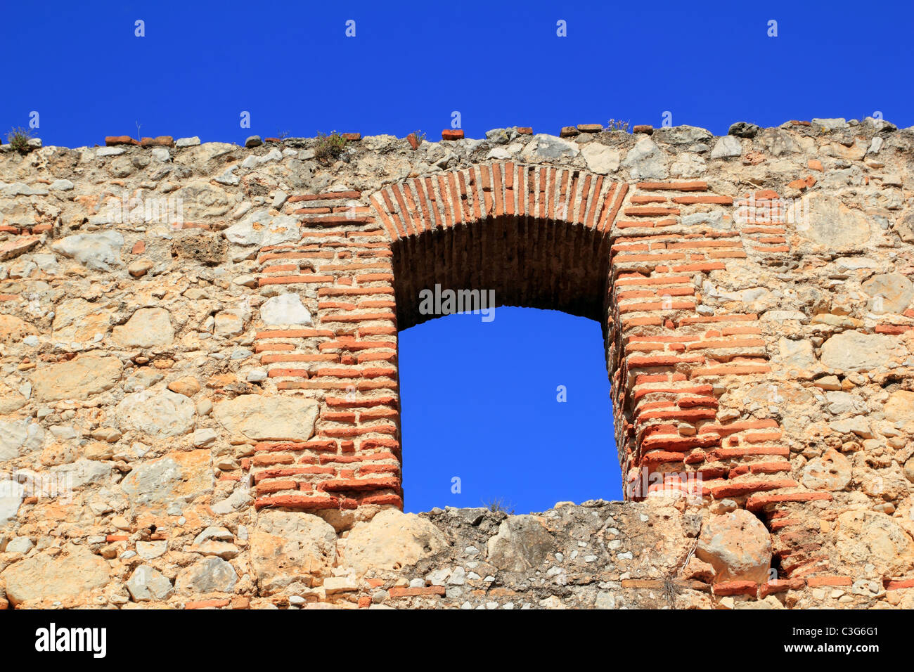 brick segmental arch in ancient masonry stone wall Spain - Stock Image