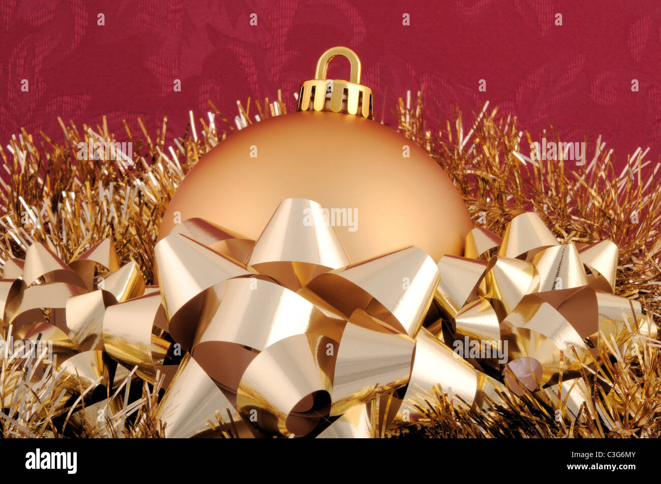 A gold Christmas ornament surrounded by garland and bows. - Stock Image