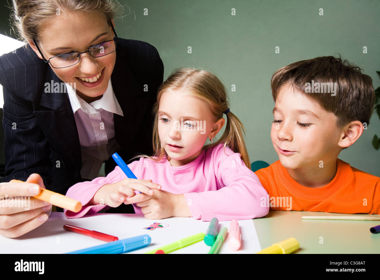 Image of smiling teacher holding highlighter and looking at girl's picture while cute boy expressing his opinion - Stock Image