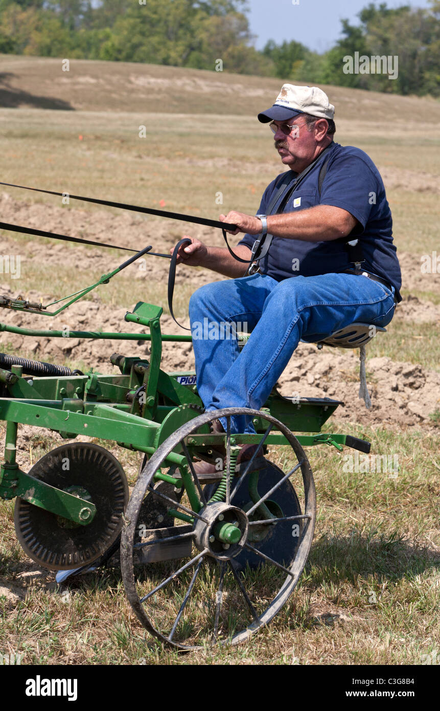 Man sitting on the back of a plow while preparing a field for planting. - Stock Image