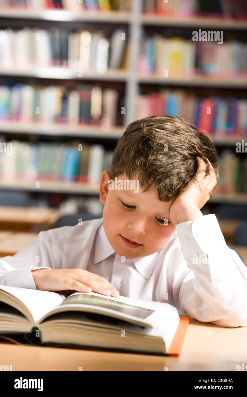 Vertical image of interested schoolkid reading book in the library - Stock Image