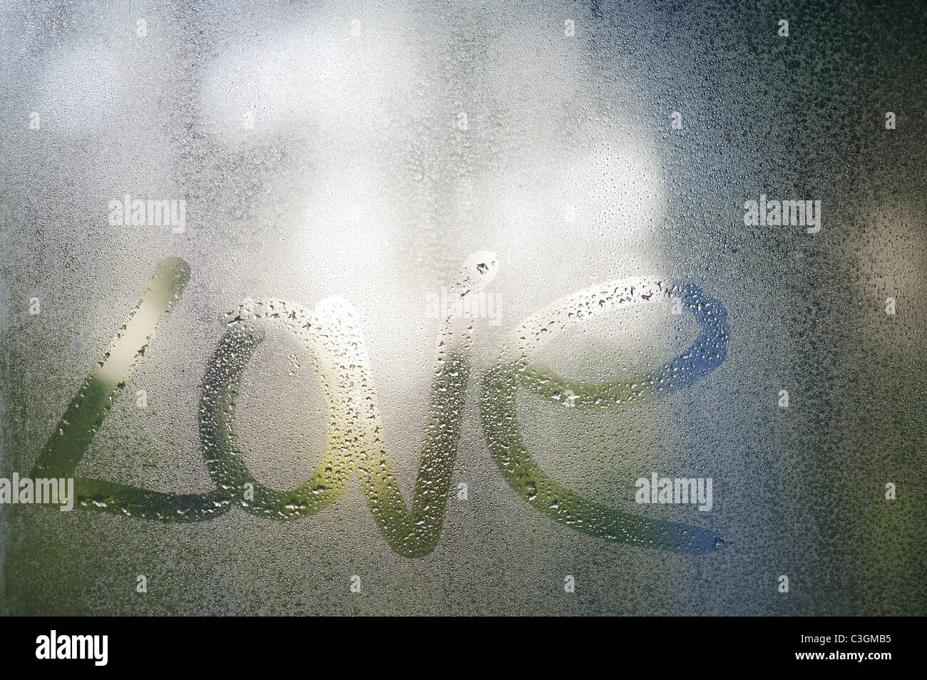 Love written in condensation on a glass window pane - Stock Image