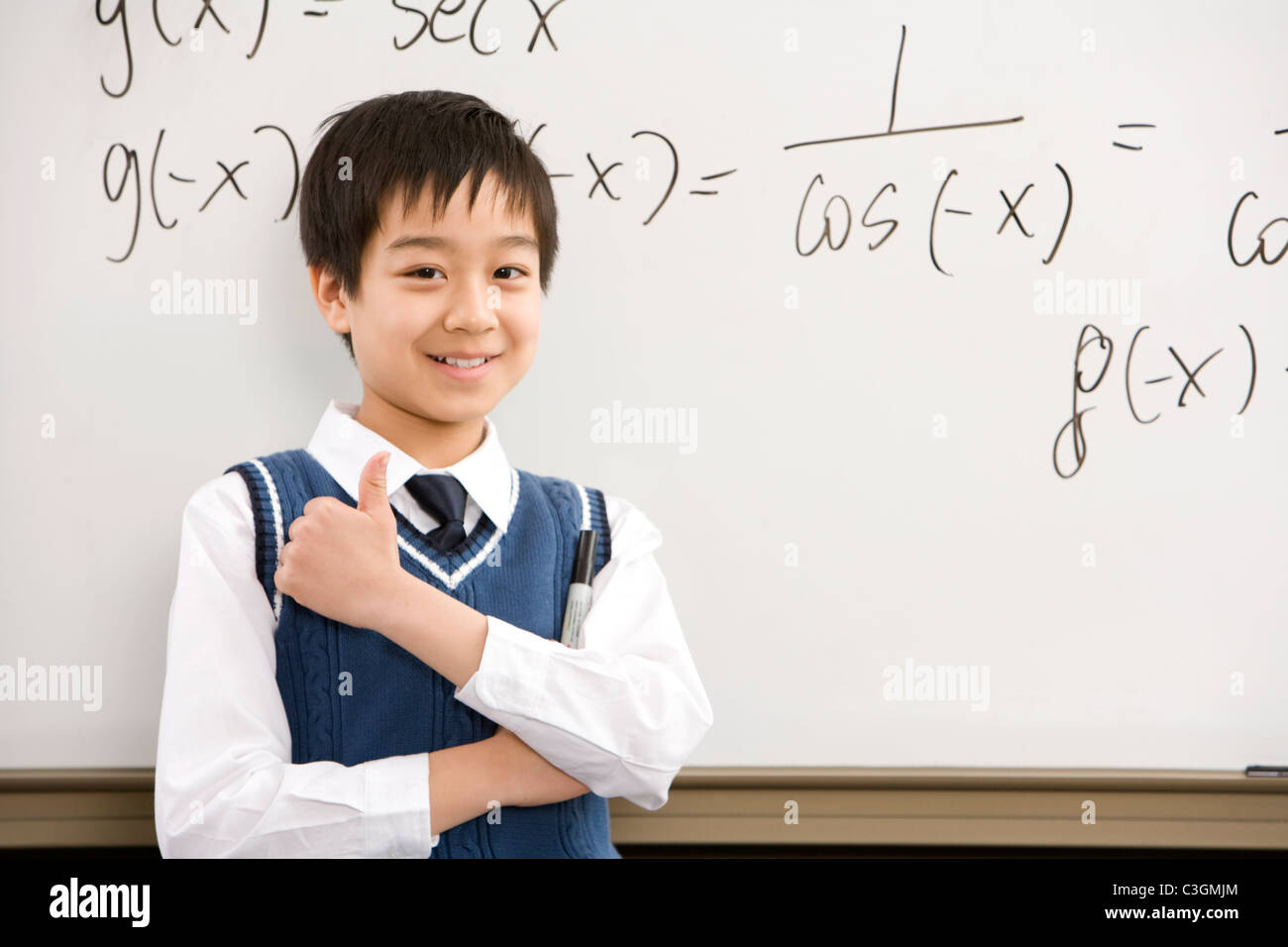 Confident student standing in front of math work Stock Photo ...