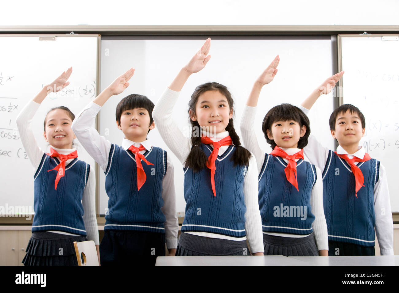 Young students saluting in a row at school - Stock Image