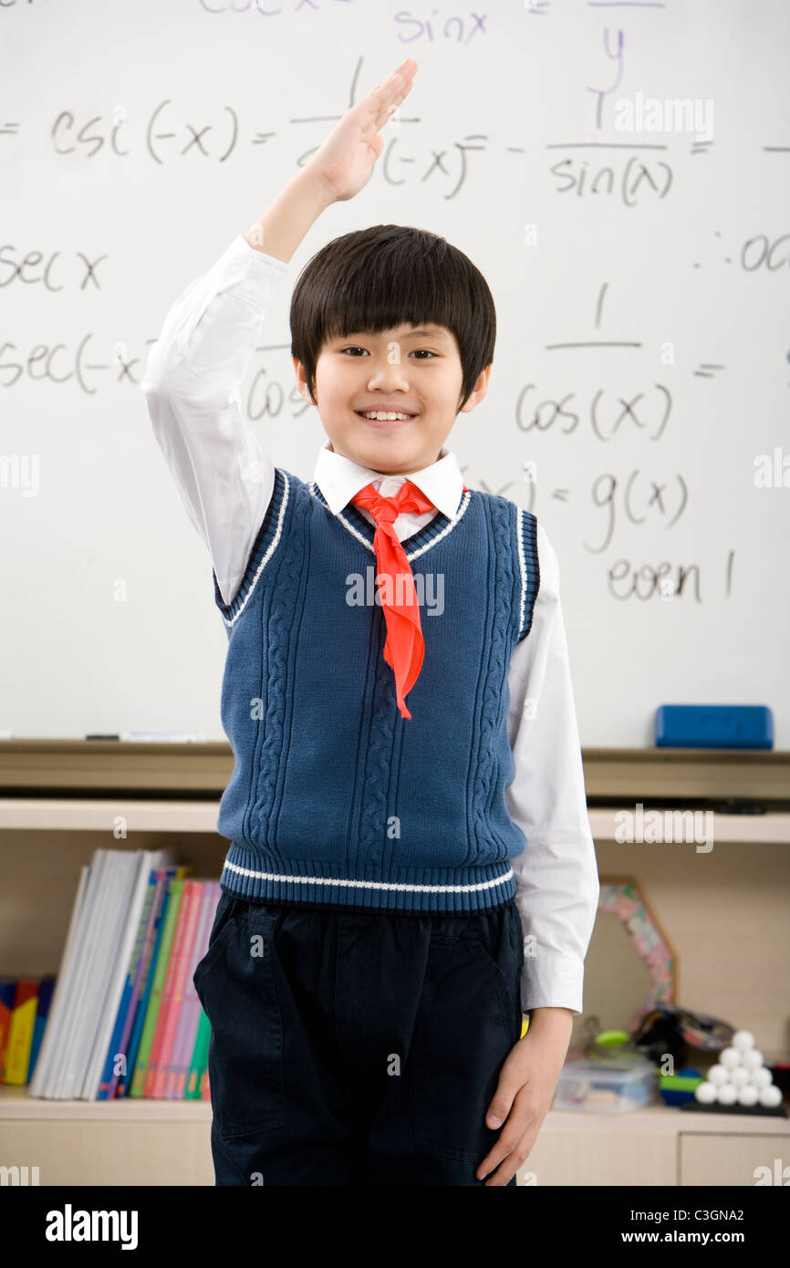 Young student saluting in front of whiteboard - Stock Image