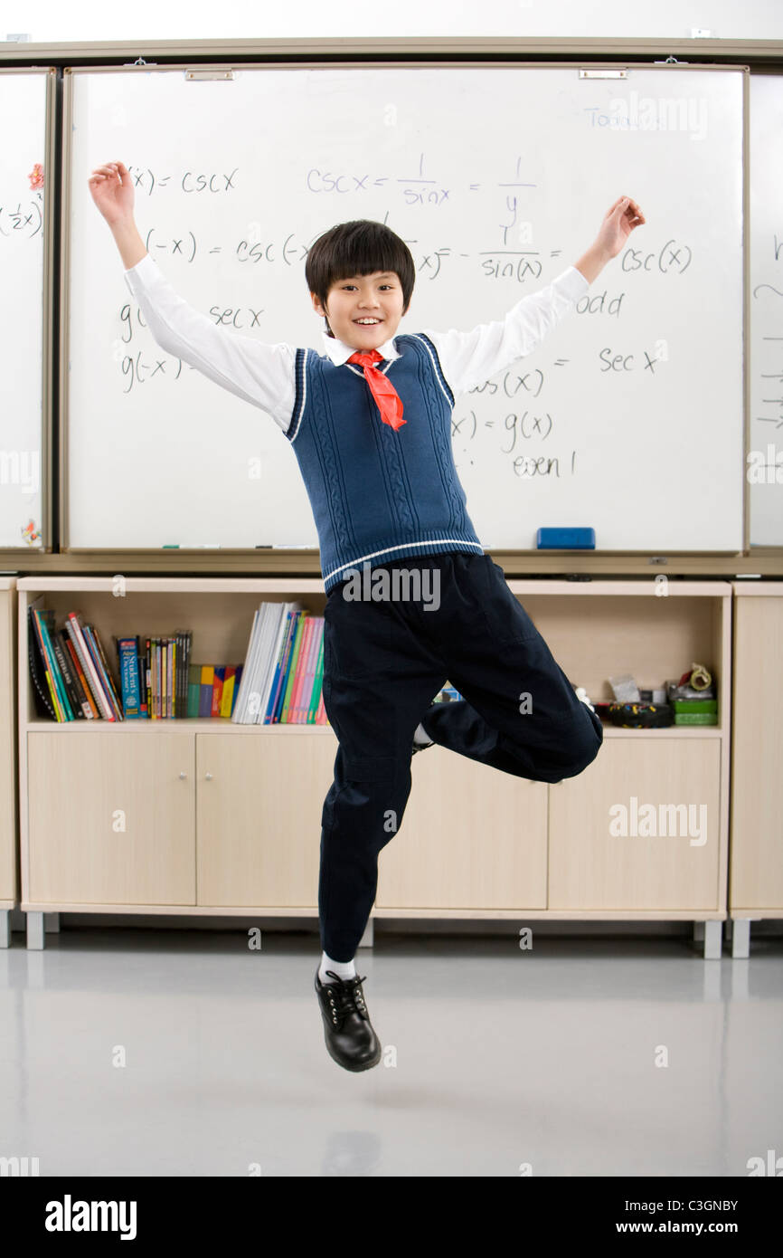 Young student jumping in front of whiteboard - Stock Image