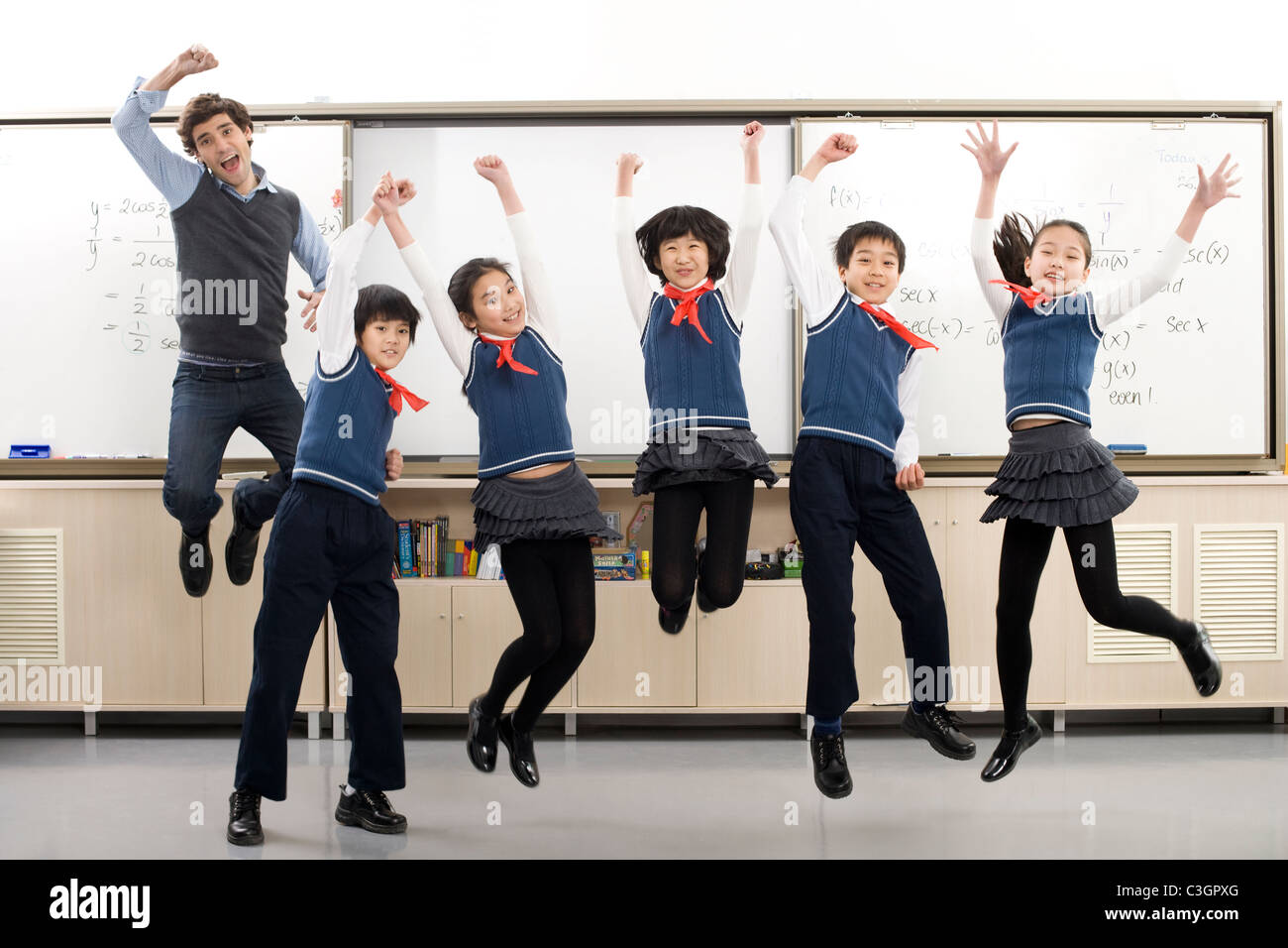 Teacher and students jumping in front of whiteboard - Stock Image