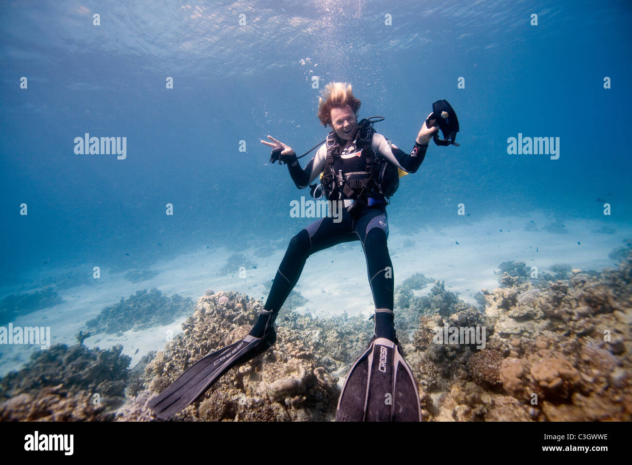 A dive instructor removes his regulator and mask and poses for a picture in the Red Sea, Dahab, Egypt - Stock Image