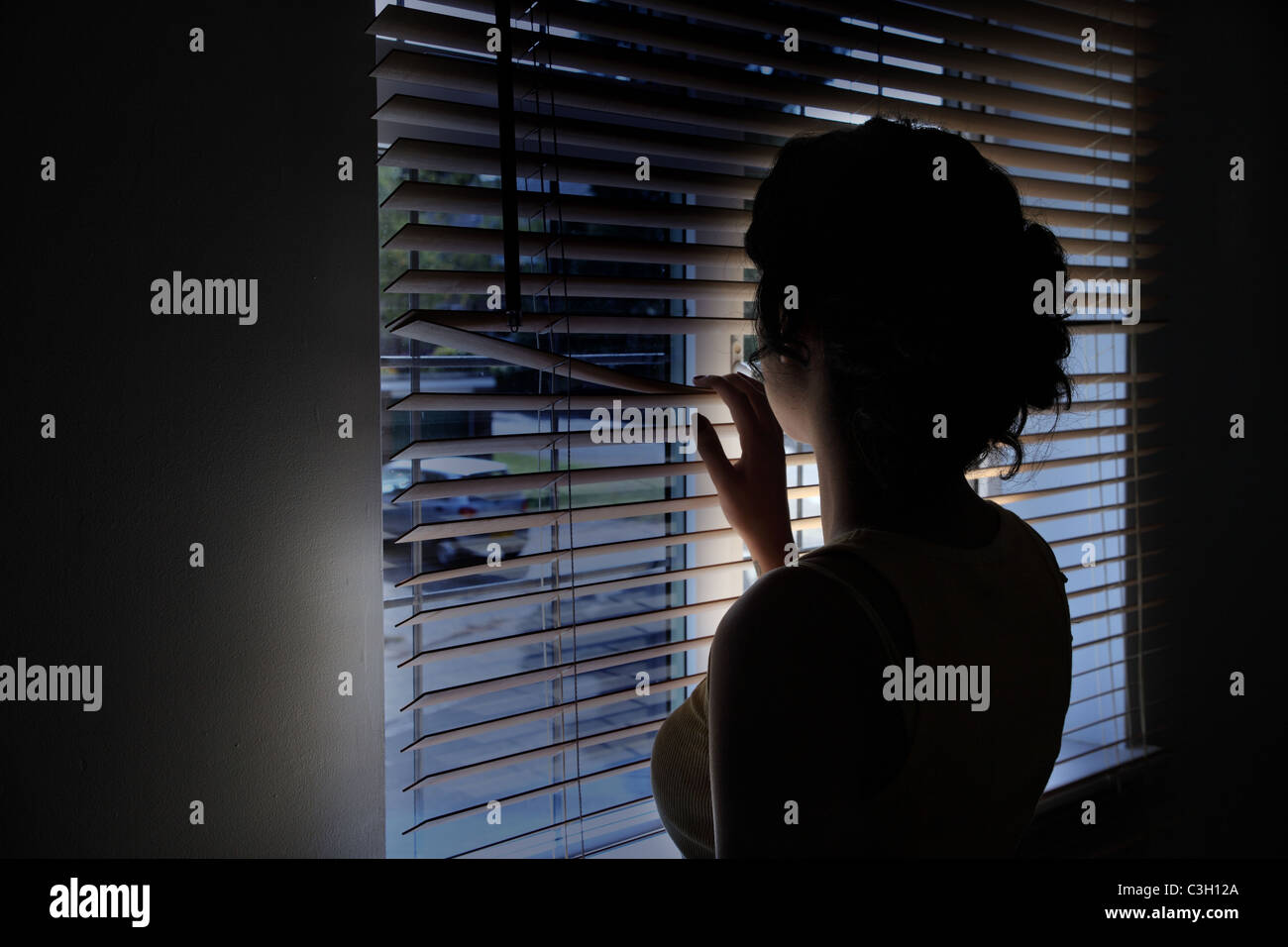 Woman looking though a window blind onto a dark empty street. Stock Photo