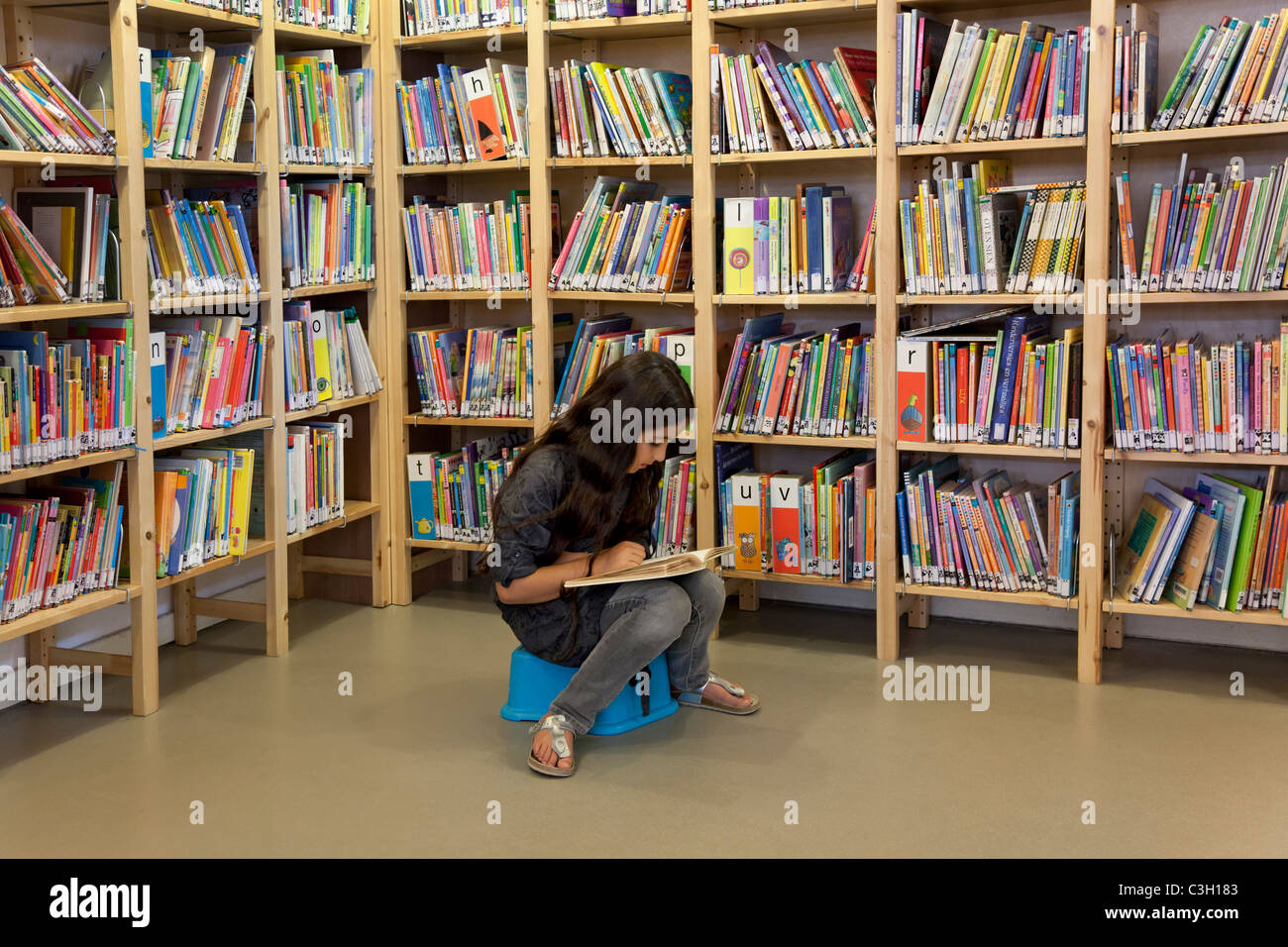Little girl reading in the library - Stock Image