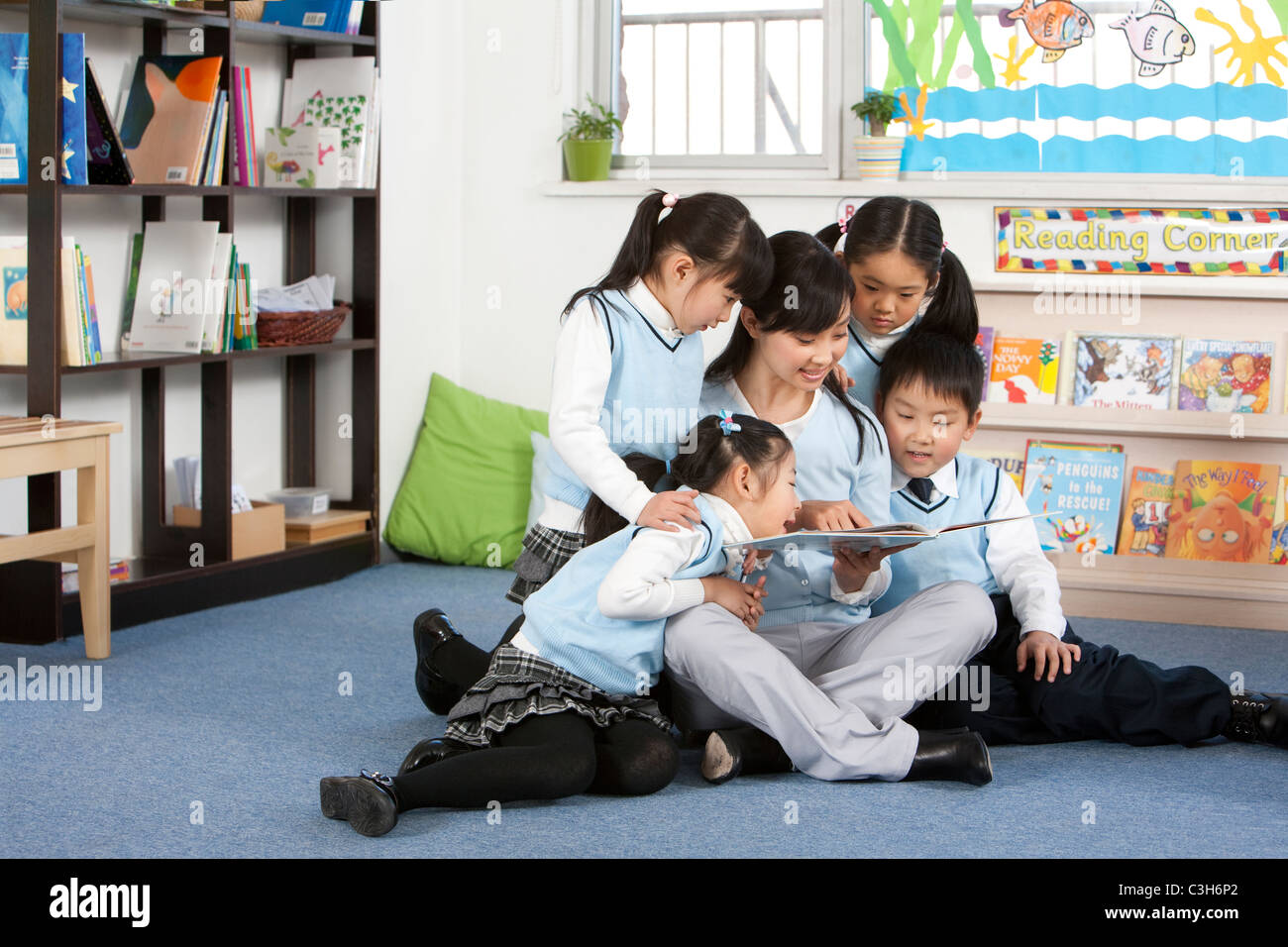 A teacher reading aloud to a classroom of students - Stock Image