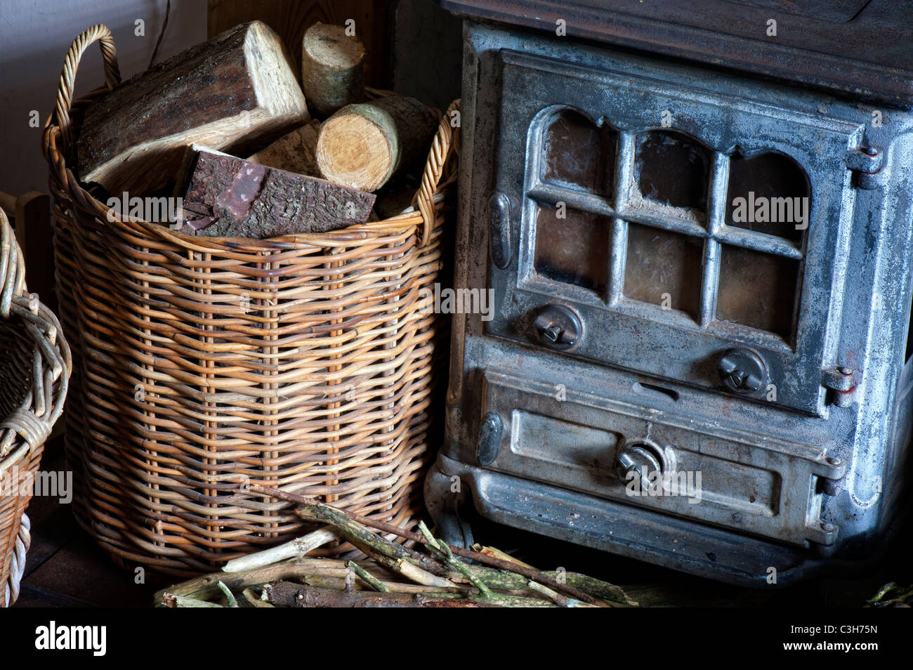 Woodburning stove and a basket of logs inside a country cottage. UK - Stock Image