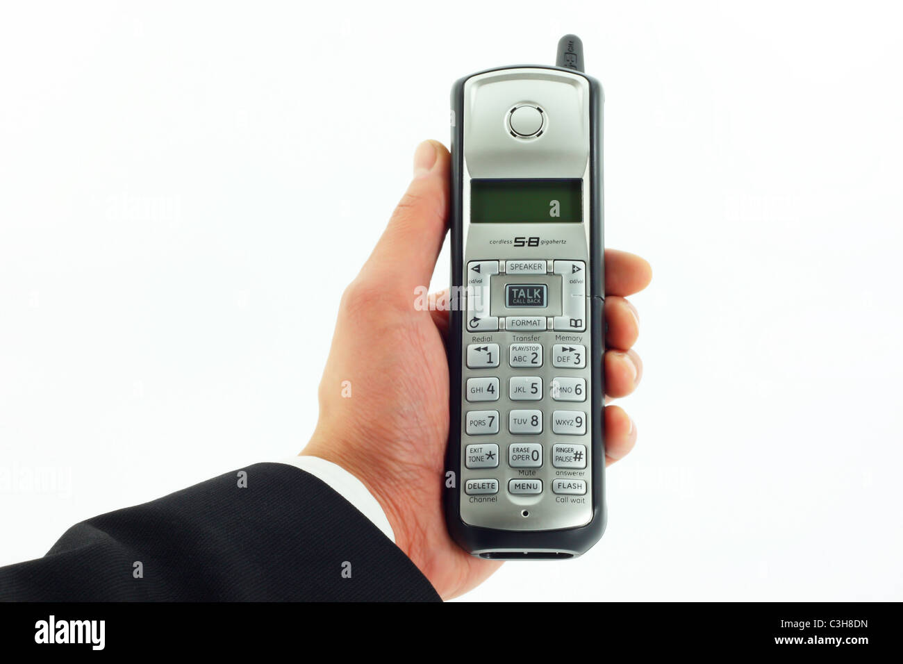 Business man's hand holding a cordless phone - Stock Image