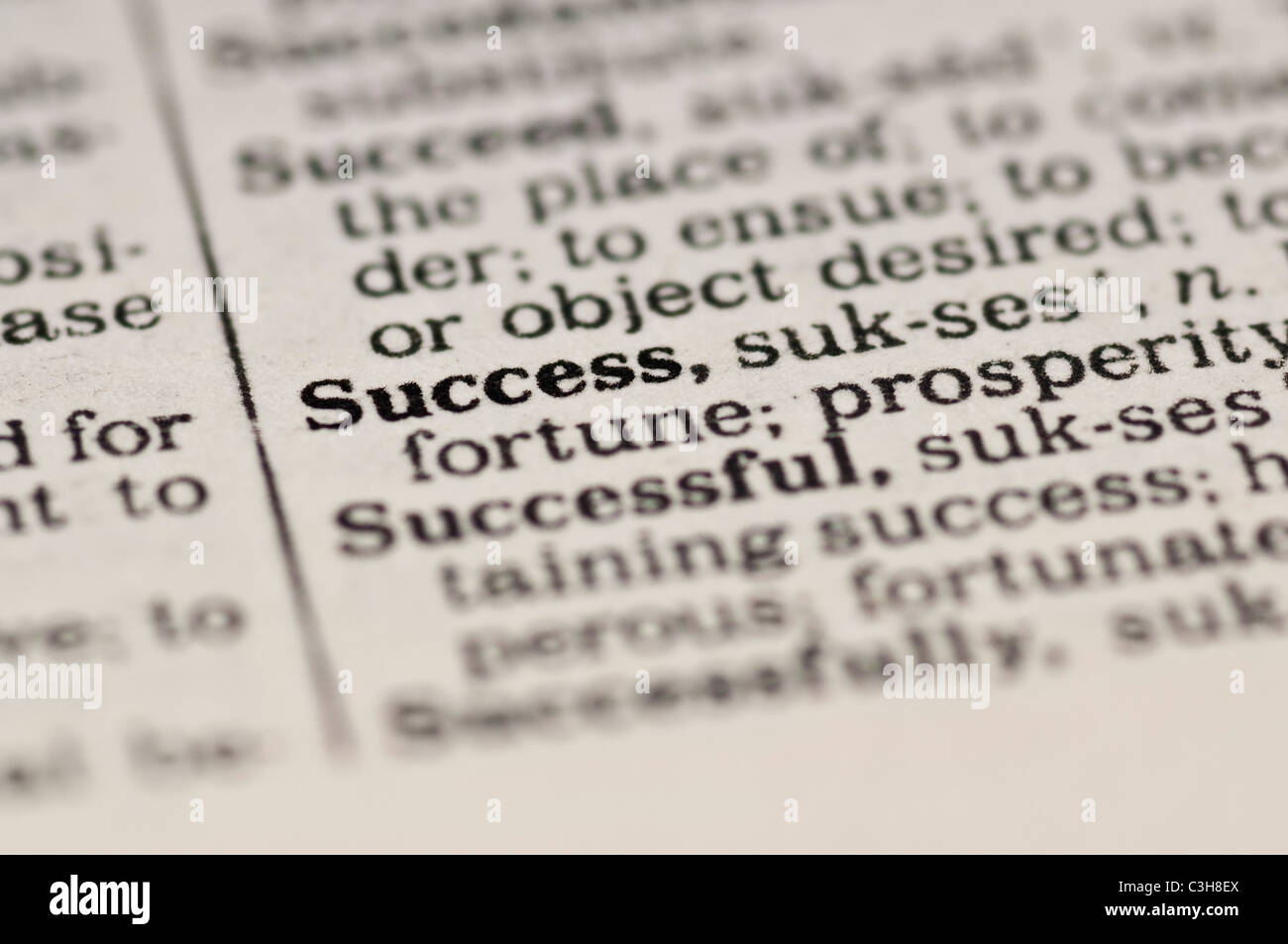 Extreme close up of the word SUCCESS found inside a dictionary - Stock Image