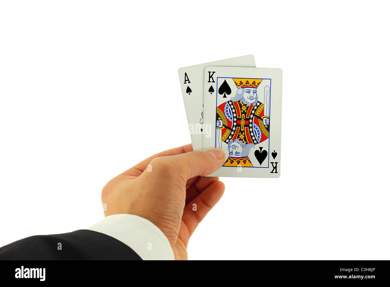 Close up of Blackjack winning cards in the hand of a suited man. - Stock Image
