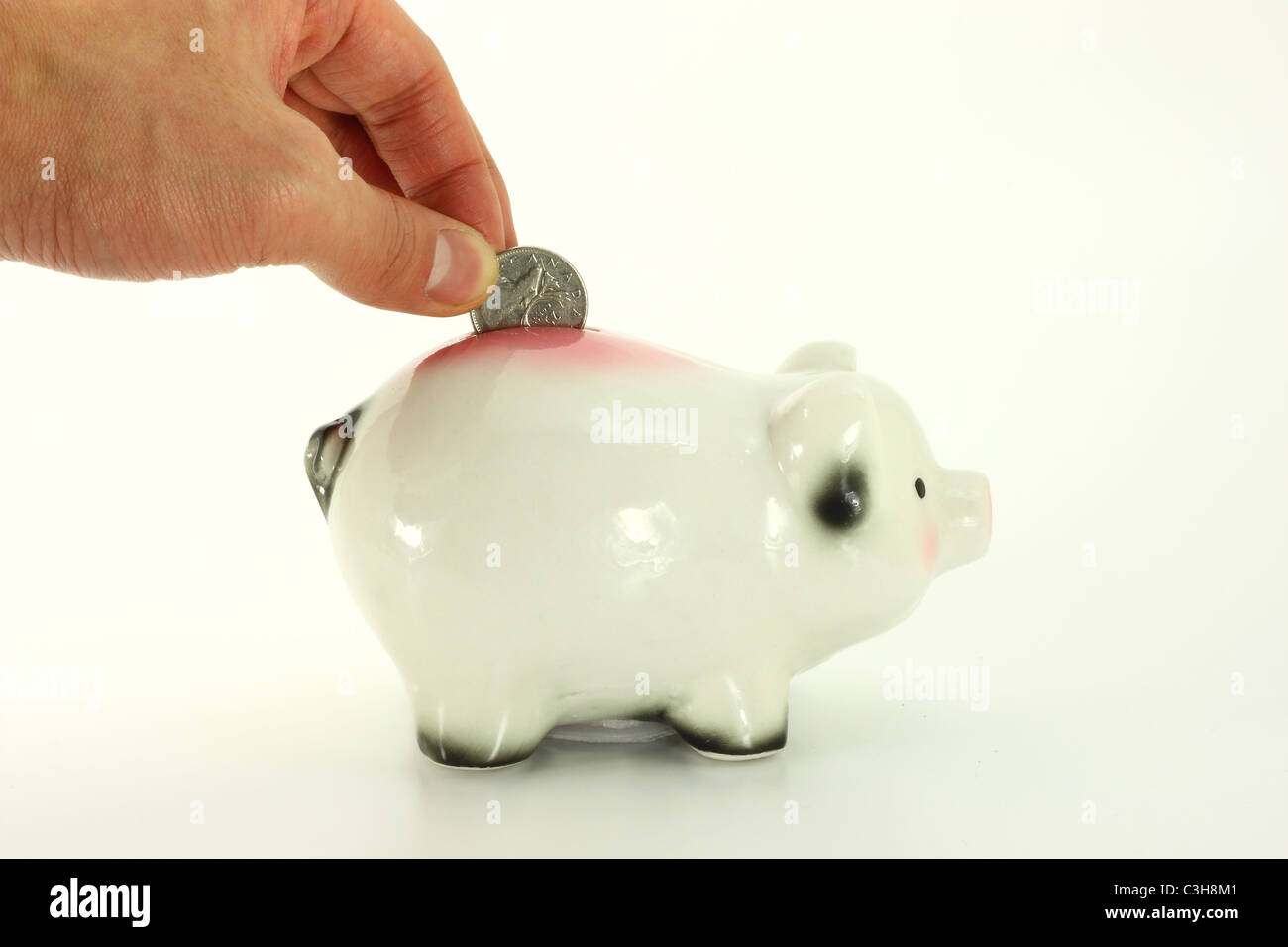 Close up of hand depositing a quarter in to a cute piggy bank isolated on a white background - Stock Image