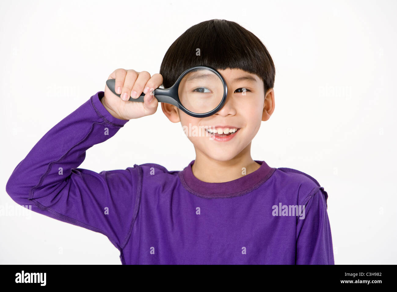 Young boy holding a magnifying glass up to his eye - Stock Image