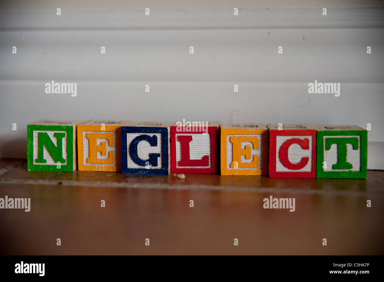 The word neglect spelled out in colourful children's block letters in a dusty corner of a house. - Stock Image