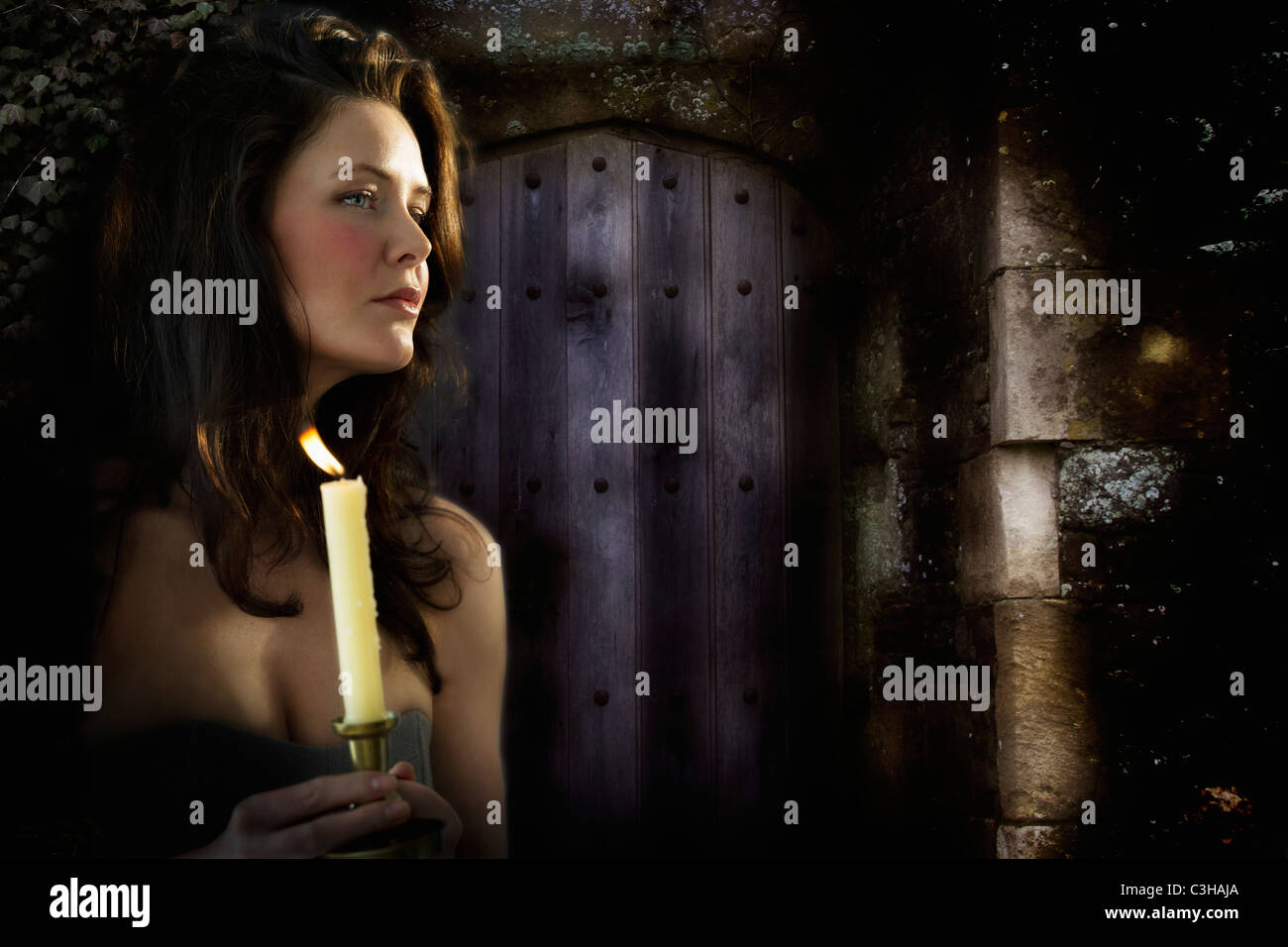 Woman with candle at night - Stock Image