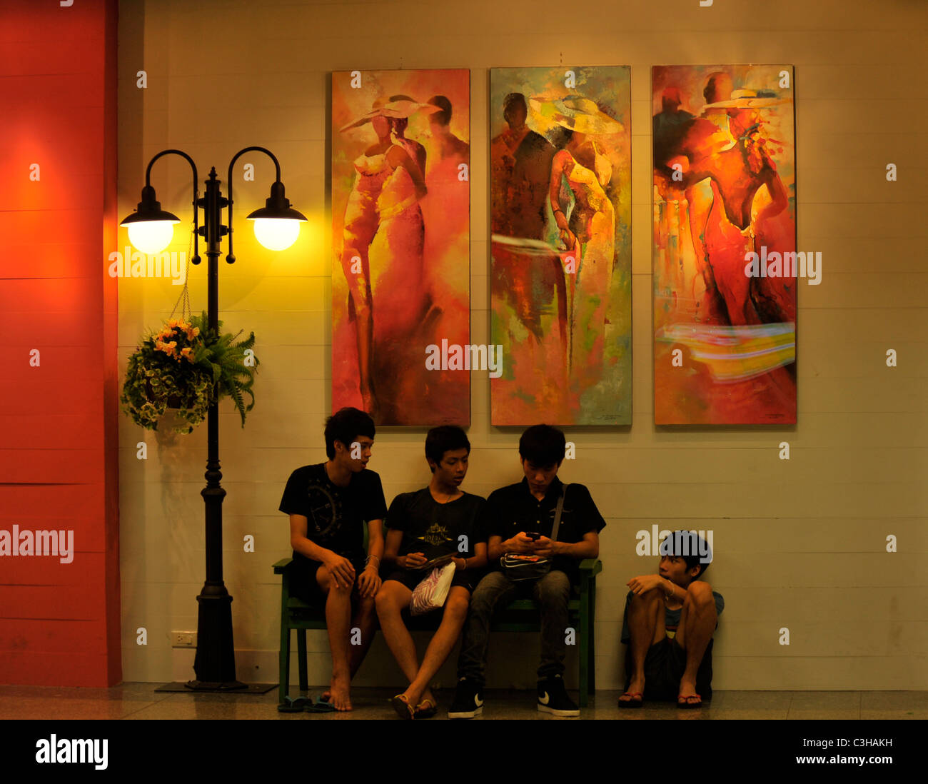 four boys and a seat made for three , subway station at chatuchak weekend market,everyday living , bangkok , Thailand - Stock Image