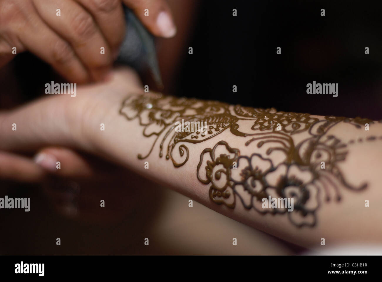 Artist appliyng henna artwork to the forearm of a Muslim bride - Stock Image