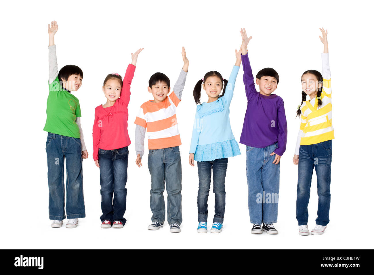 A group of children holding their hands in the air - Stock Image