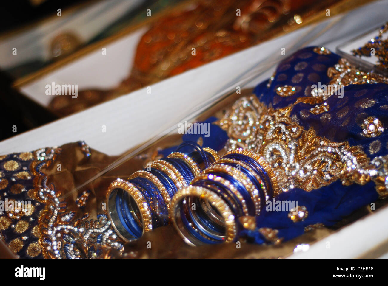 Colourful bangles and elaborate clothes assembled as gifts for a Muslim bride as part of her wedding ceremony. - Stock Image