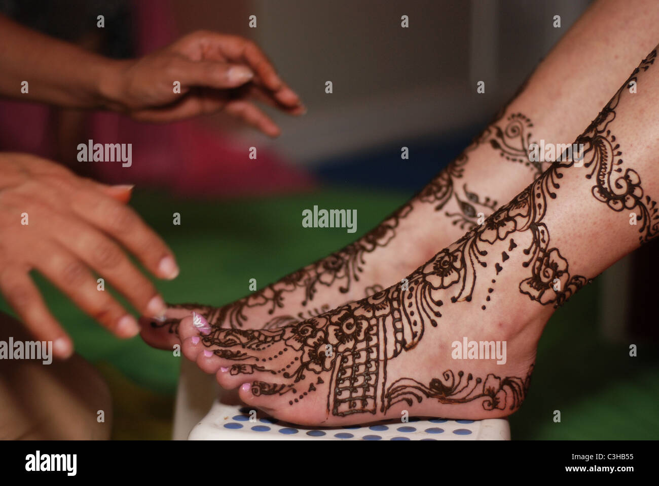 Artist having Completed Mehndi Application to the Feet of a Bride - Stock Image