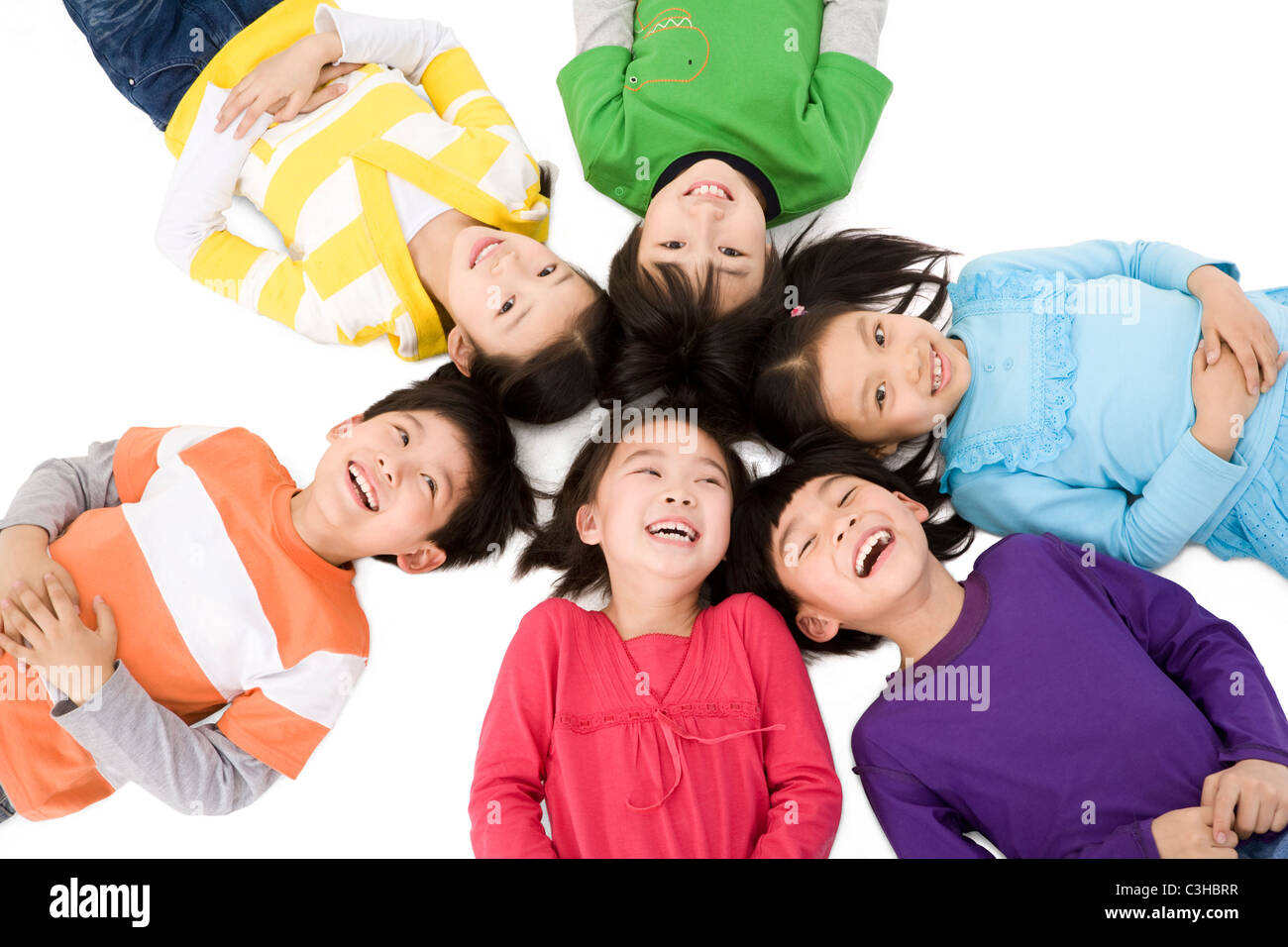 A group of children lying in a circle - Stock Image