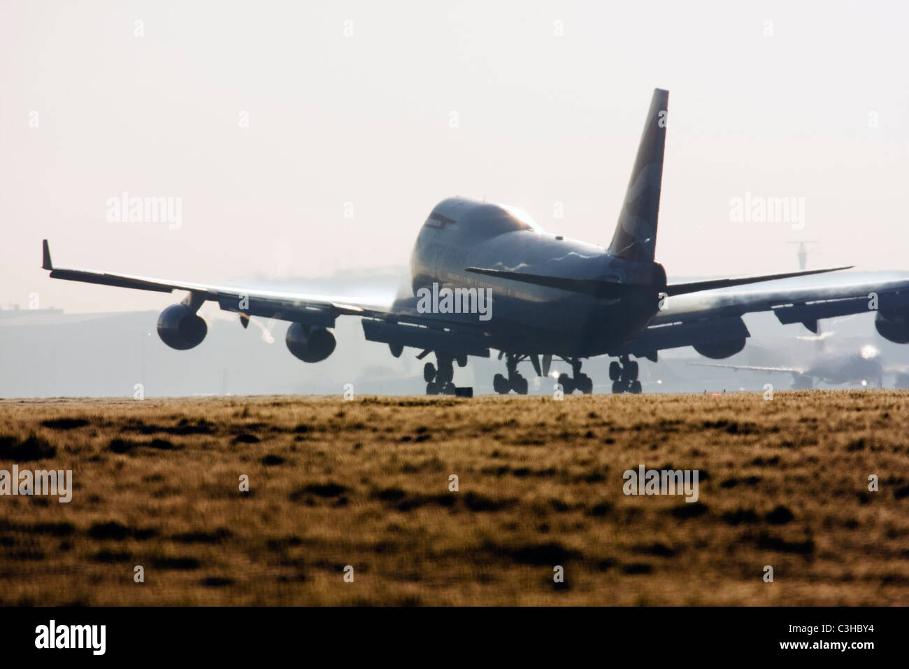 British Airways Boeing 747 landing at London Heathrow with condensation trails forming over the wings. - Stock Image