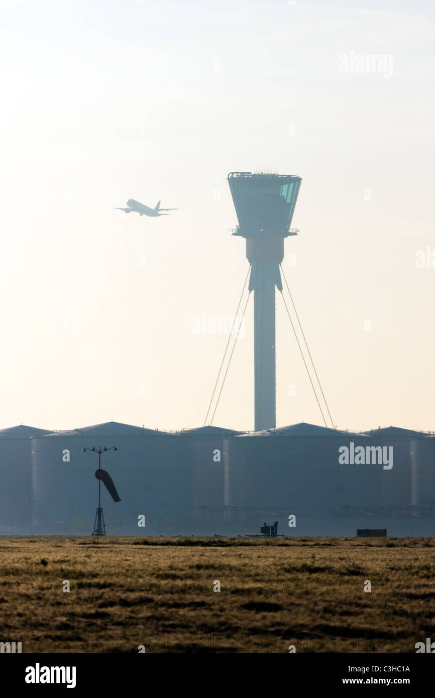 Comercial airliner taking off and London's Heathrow control tower. - Stock Image