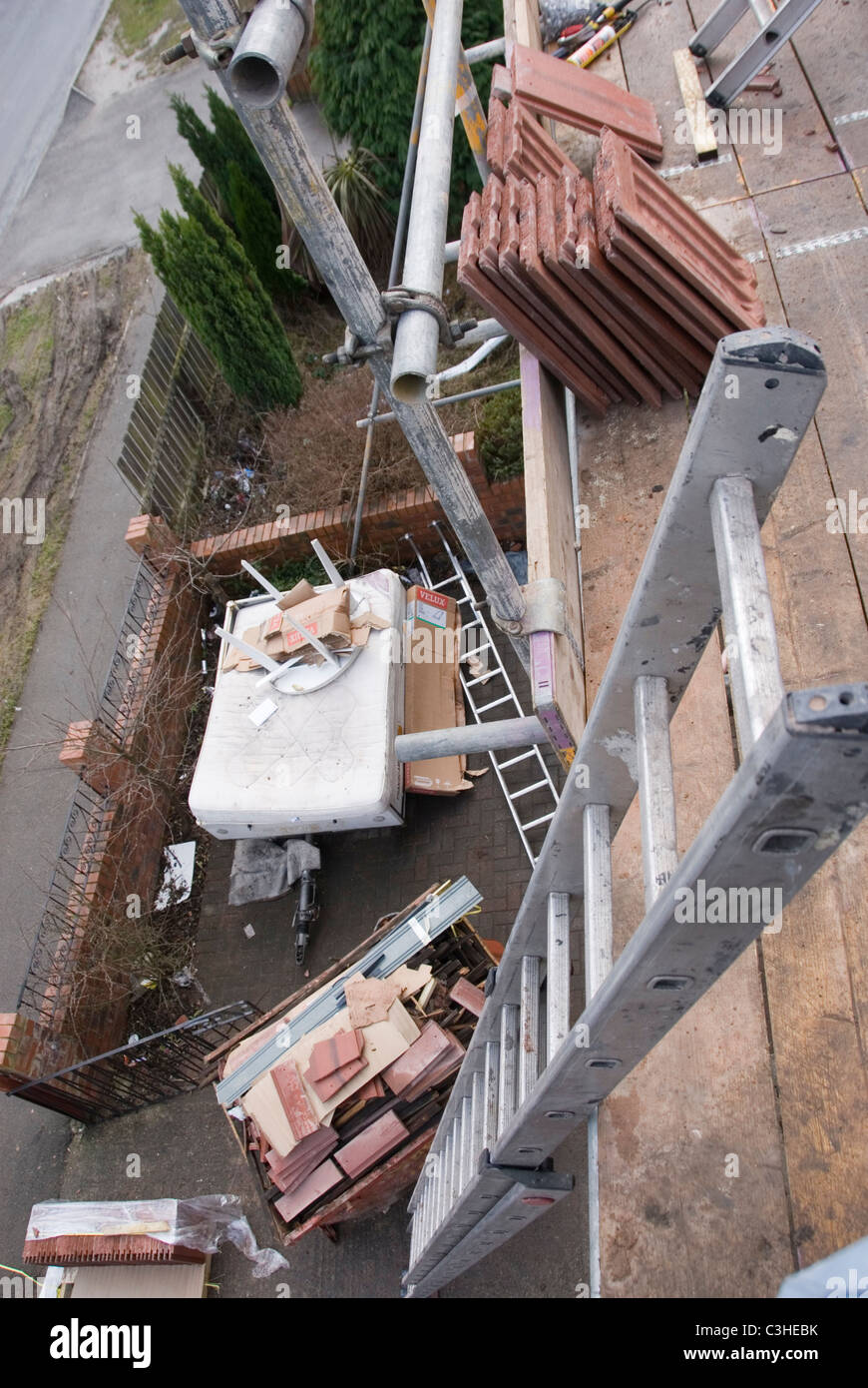 Top of Ladder & Full Skip in Garden Below, View from Scaffolding, Re Roofing Residential Home, Ontop Roofing, Sheffield, Stock Photo