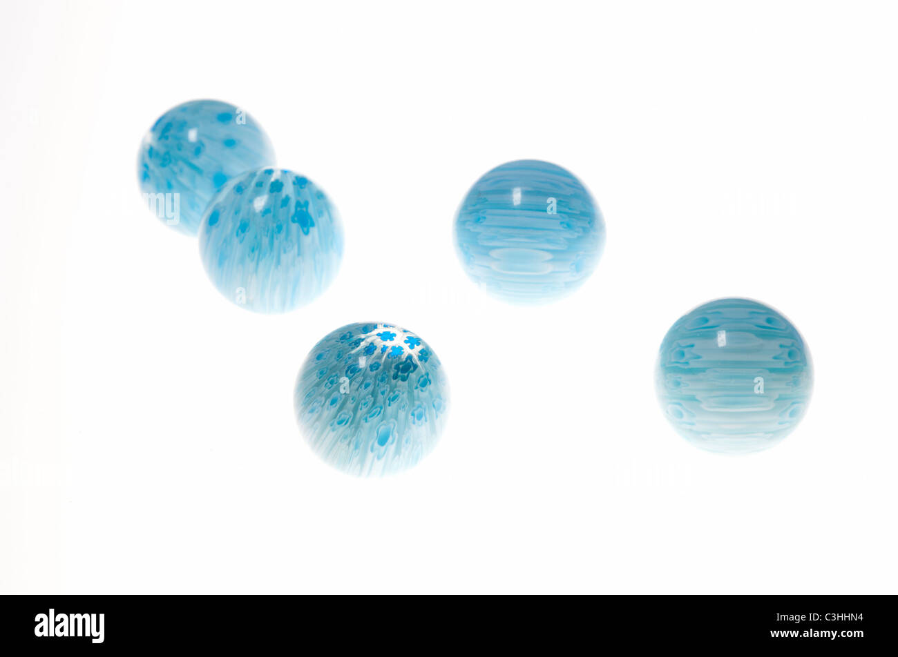 5 blue marbles on white - Stock Image