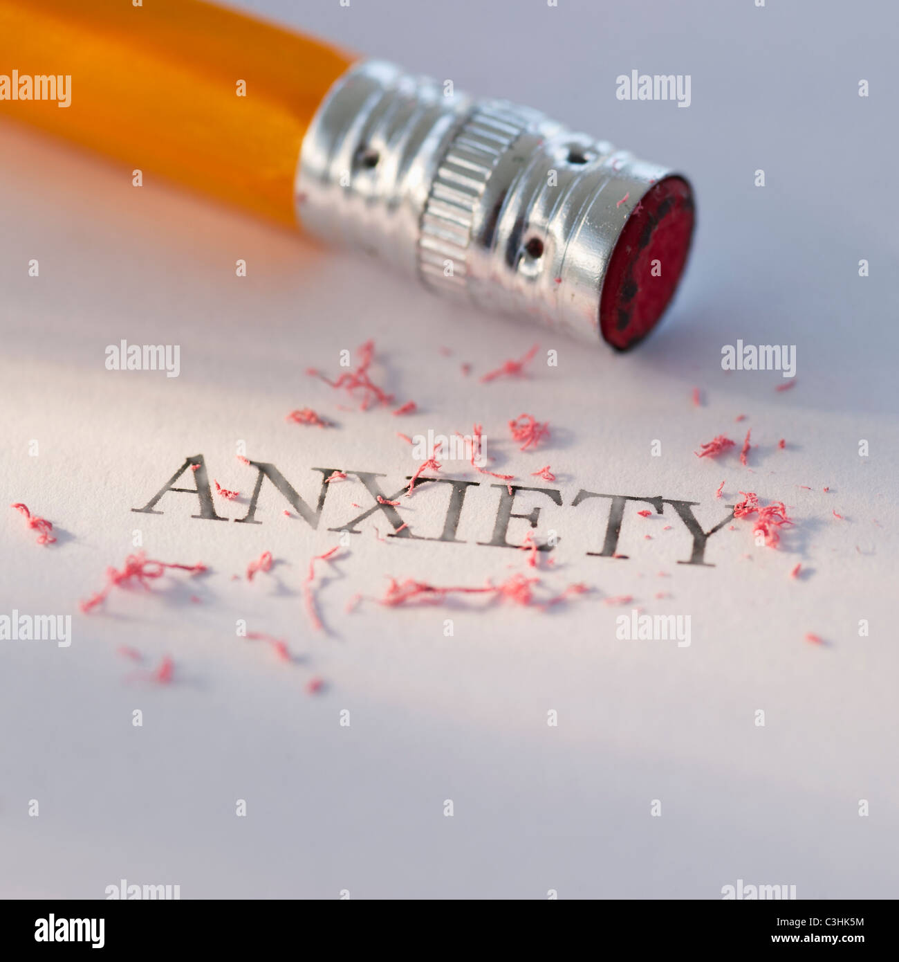 Studio shot of pencil erasing the word anxiety from piece of paper - Stock Image