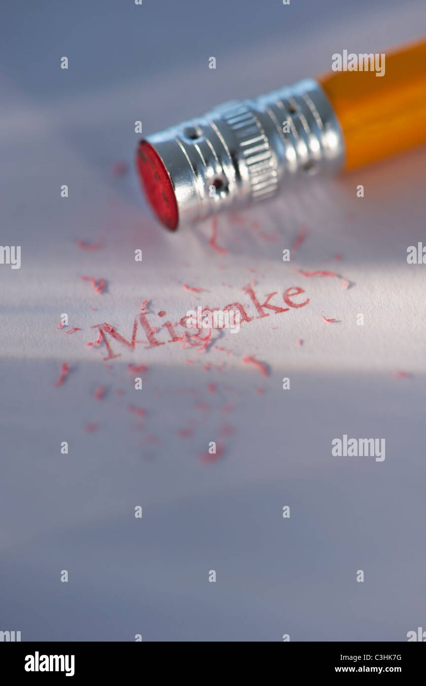 Studio shot of pencil erasing the word mistake from piece of paper - Stock Image