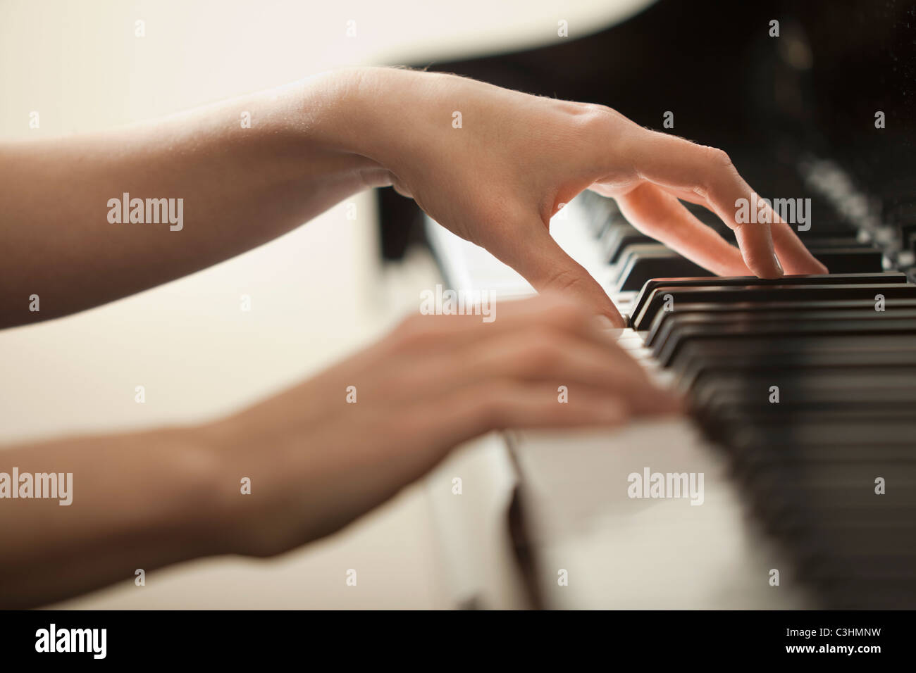 Young woman hands playing piano - Stock Image