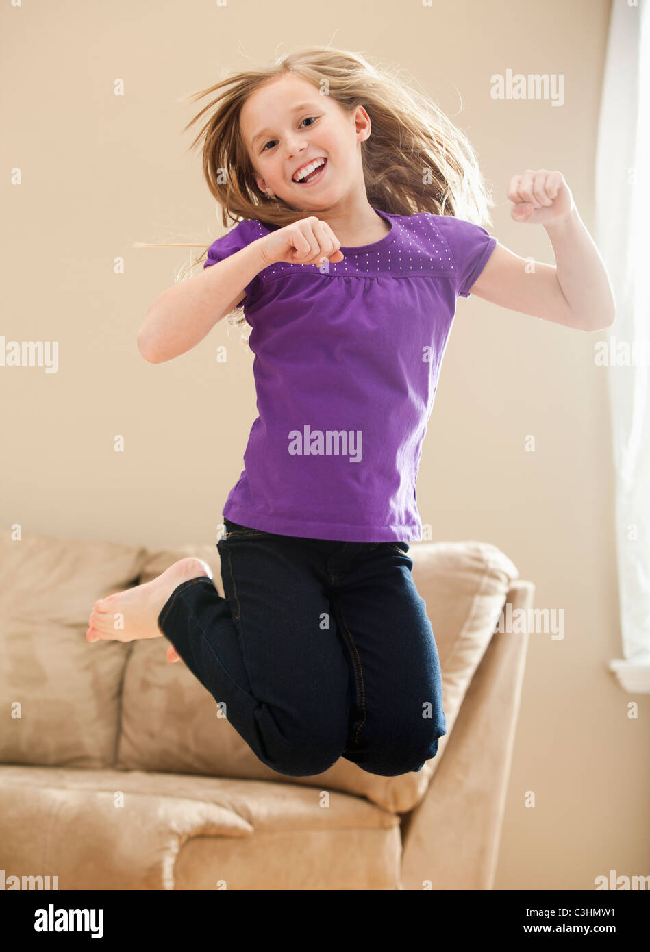 Portrait of girl (8-9) jumping - Stock Image