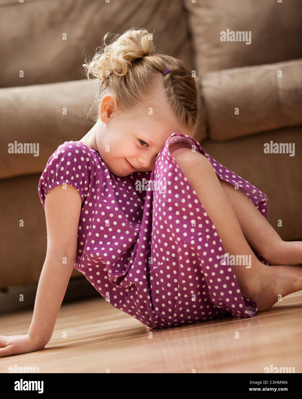Shy girl (2-3) slitting on floor Stock Photo