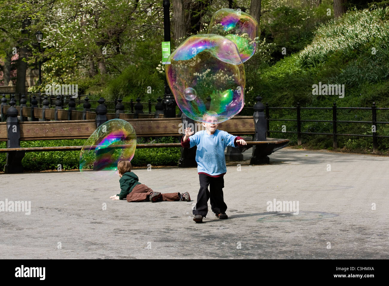 Two young boys chasing huge soap bubbles in a city park - Stock Image