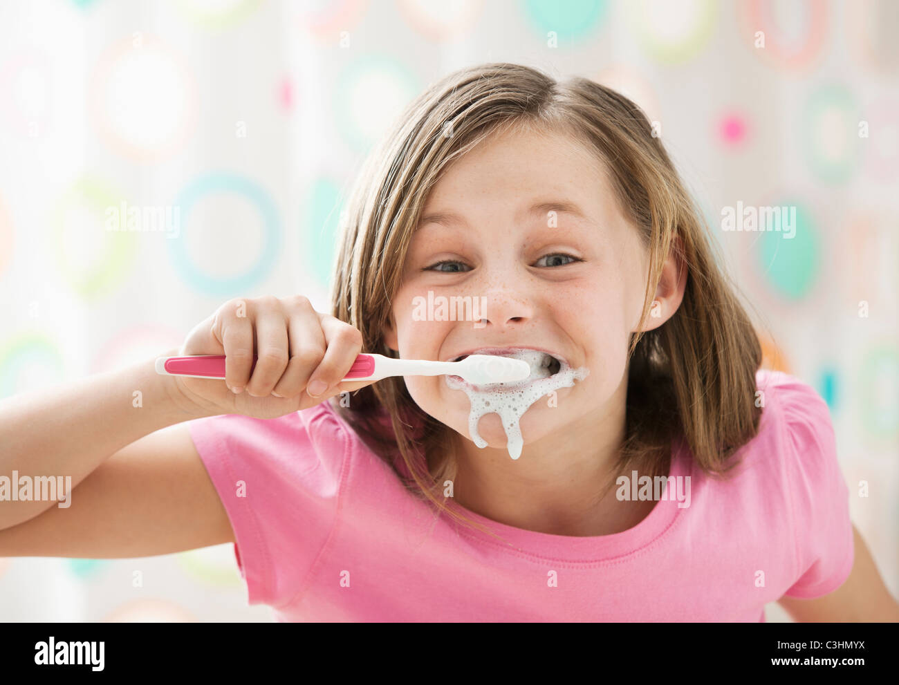 Girl (10-11) brushing teeth in messy way - Stock Image