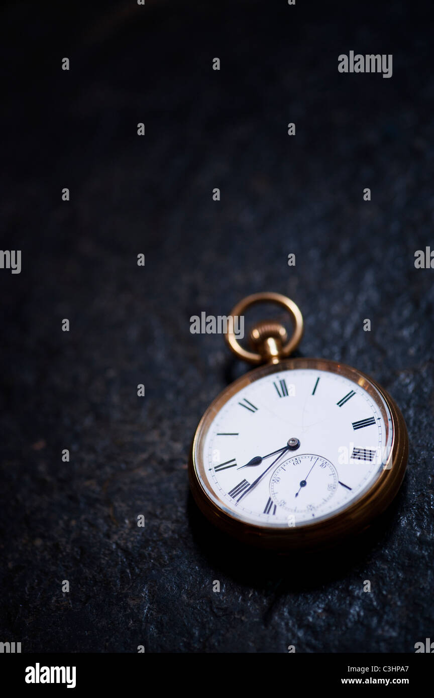 Old open face pocket watch on slate Stock Photo