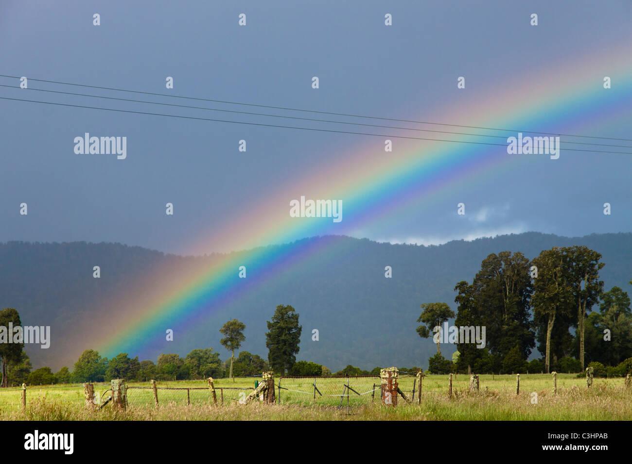 Rainbow, rural landscape, Fox Glacier, West Coast, New Zealand - Stock Image