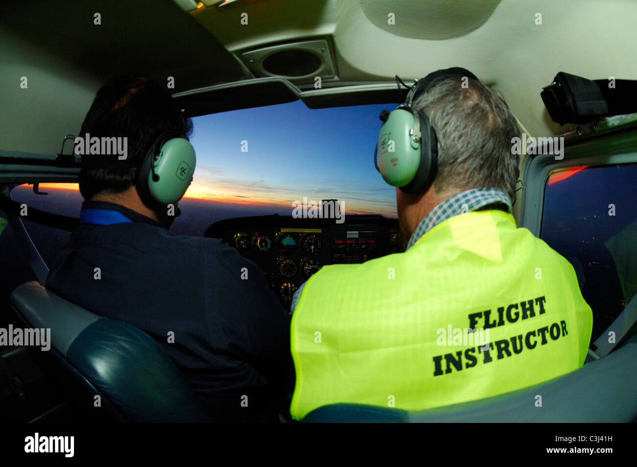 Flying instructor with student pilot during a night flight in a Cessna 172 over  Luxembourg country - Stock Image