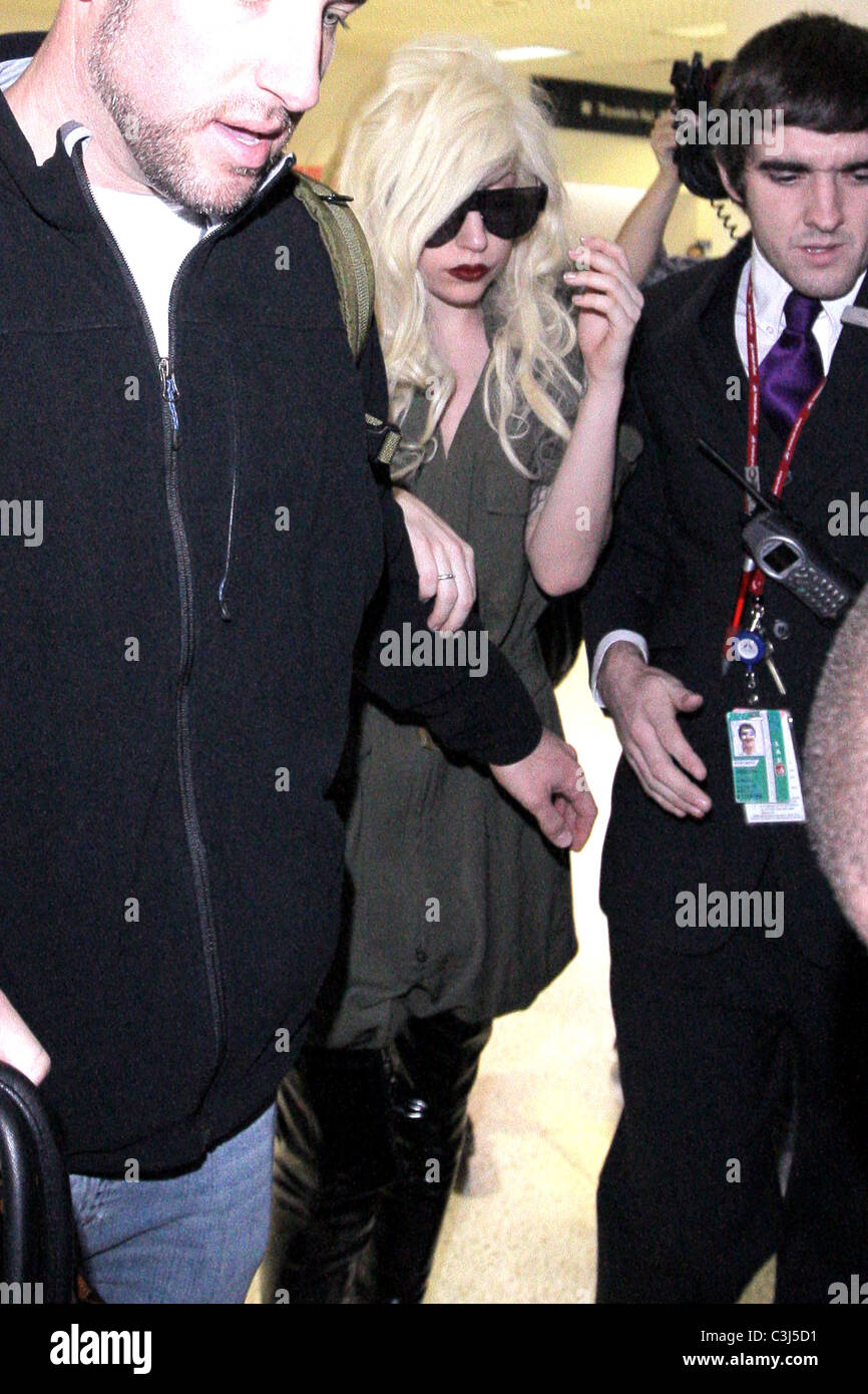 Lady Gaga is surrounded by paparazzi as she arrives at LAX