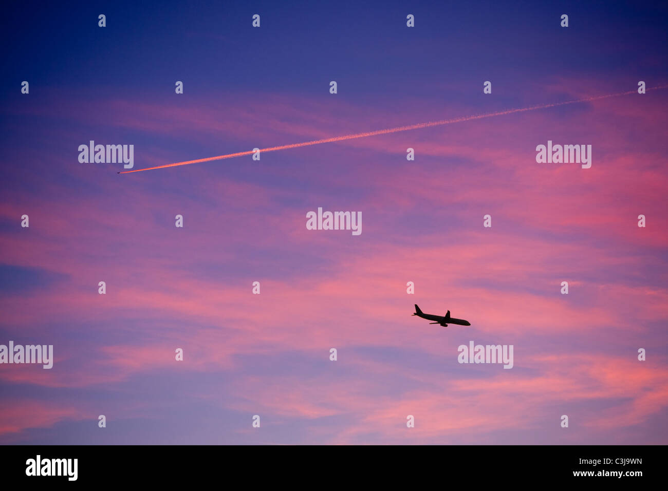 plane contrail at sunset near Windermere UK Stock Photo