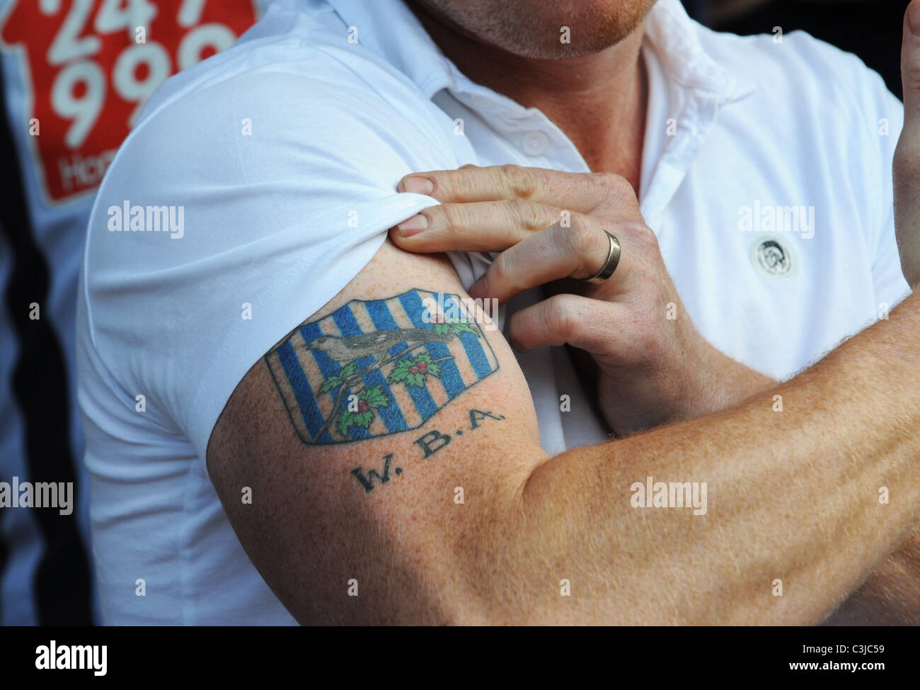 Football supporter showing his club badge tattoo - Stock Image