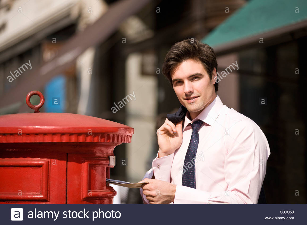 A businessman posting letters in a letterbox Stock Photo